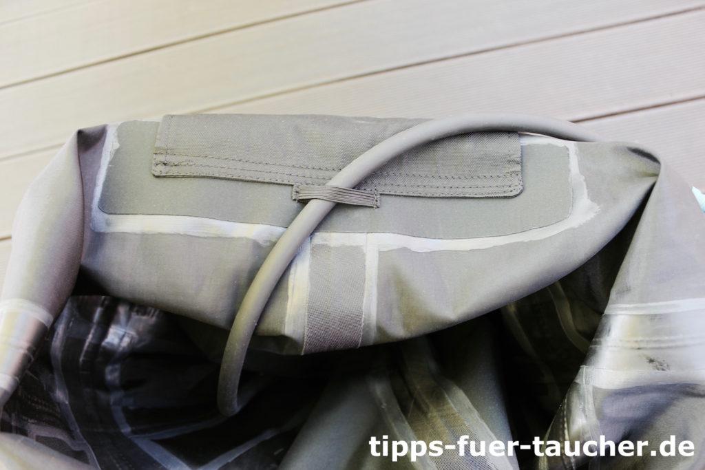 Kleine Schlaufe auf der Innenseite des Trockentauchanzugs, die den Schlauch des P-Valves in Position hält